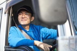 トラックを運転する作業着姿の男性の写真素材 [FYI04782639]
