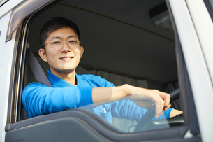 トラックを運転する作業着姿の男性の写真素材 [FYI04782640]