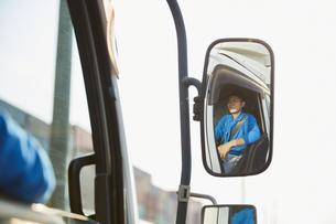 トラックを運転する作業着姿の男性の写真素材 [FYI04782641]