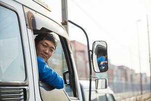 トラックを運転する作業着姿の男性の写真素材 [FYI04782642]