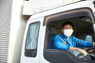 トラックを運転する作業着とマスクを着用した男性の写真素材 [FYI04782643]