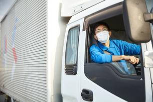 トラックを運転する作業着とマスクを着用した男性の写真素材 [FYI04782644]