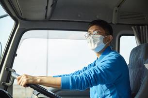 トラックを運転する作業着とマスクを着用した男性の写真素材 [FYI04782645]