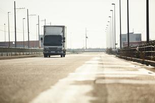 真っ直ぐな道路を走るトラックの写真素材 [FYI04782647]
