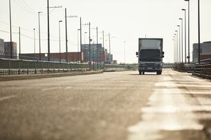 真っ直ぐな道路を走るトラックの写真素材 [FYI04782649]
