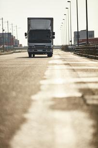 真っ直ぐな道路を走るトラックの写真素材 [FYI04782650]