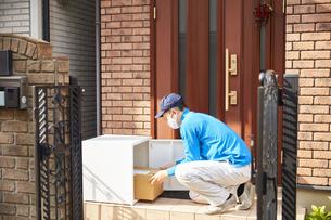 宅配ボックスに配達物を入れる作業着姿の男性の写真素材 [FYI04782651]