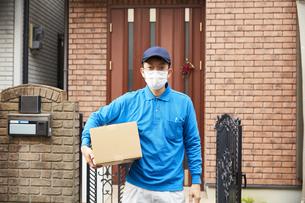 家の前に立つ作業着とマスクを着用した男性の配達員の写真素材 [FYI04782654]