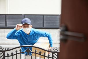 扉の向こうで挨拶をするマスクをした男性の宅配員の写真素材 [FYI04782655]