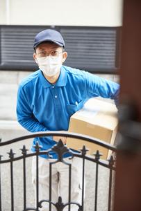 扉の向こうで挨拶をするマスクをした男性の宅配員の写真素材 [FYI04782656]