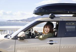 車の助手席で窓の外を見て笑う女性の写真素材 [FYI04782716]
