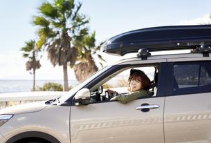 車の助手席で窓の外を見て笑う女性の写真素材 [FYI04782721]