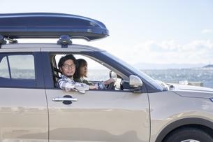車の助手席で窓の外を見て笑う女性の写真素材 [FYI04782725]