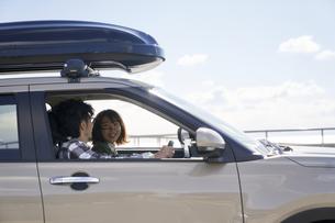 車の中で笑顔で話す男女の写真素材 [FYI04782728]
