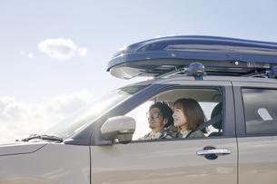 車の中で笑顔で話す男女の写真素材 [FYI04782729]