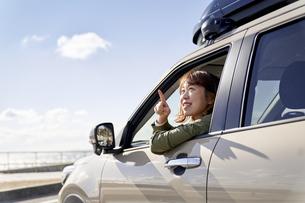 車の助手席で窓の外を見て笑う女性の写真素材 [FYI04782730]
