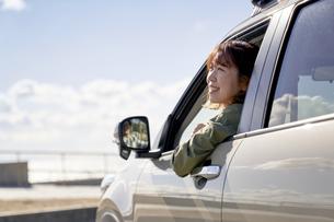 車の助手席で窓の外を見て笑う女性の写真素材 [FYI04782731]