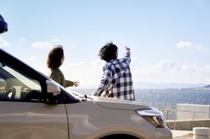 車の横で遠くを指差す男女の写真素材 [FYI04782732]