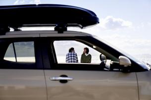 車の向こうで話す男女の写真素材 [FYI04782733]