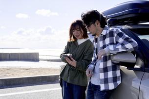 車の横でスマートフォンをみて話す男女の写真素材 [FYI04782734]