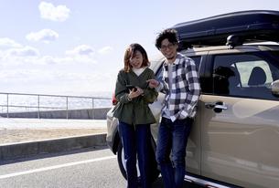 車の横でスマートフォンをみて話す男女の写真素材 [FYI04782735]