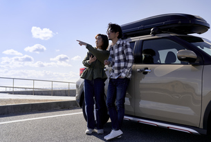 車の横で遠くを指差す男女の写真素材 [FYI04782736]