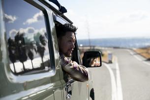 車の窓から体を乗り出す男性の写真素材 [FYI04782738]