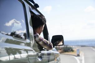 車の窓から体を乗り出して前を見る男性の写真素材 [FYI04782739]