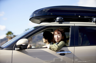 車の助手席で窓の外を見て笑う女性の写真素材 [FYI04782740]
