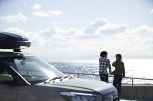 車の向こうで海を見ながら話す男女の写真素材 [FYI04782741]