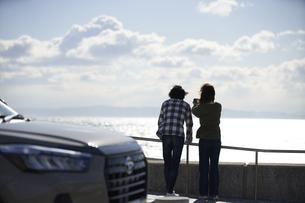 車の向こうで海を見ながら話す男女の写真素材 [FYI04782742]