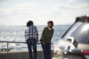 車の向こうで海を見ながら話す男女の写真素材 [FYI04782743]