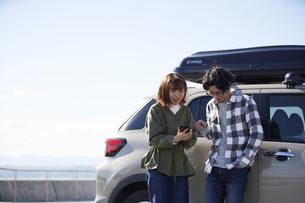 車の横でスマートフォンをみて話す男女の写真素材 [FYI04782744]