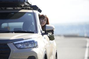 車の窓から顔を出して笑う女性の写真素材 [FYI04782746]