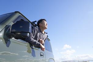 車の助手席の窓から体を乗り出す男性の写真素材 [FYI04782752]