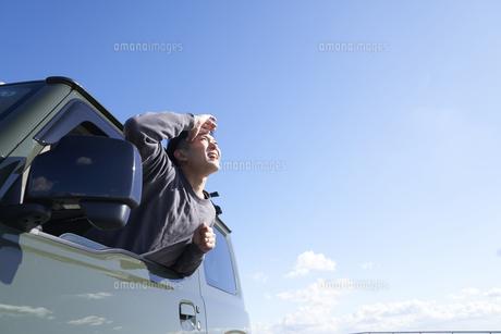 車の助手席の窓から体を乗り出す男性の写真素材 [FYI04782753]