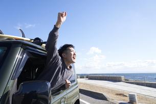 車の助手席の窓から体を乗り出す男性の写真素材 [FYI04782754]