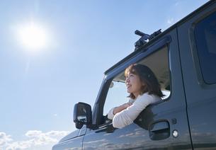 車の助手席で窓の外を見て笑う女性の写真素材 [FYI04782755]