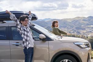 車から降りて伸びをする男女の写真素材 [FYI04782756]