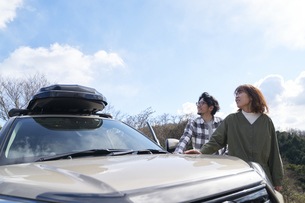 車の横で空を見上げる男女の写真素材 [FYI04782760]