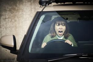 車を運転している驚いた表情の女性の写真素材 [FYI04782763]