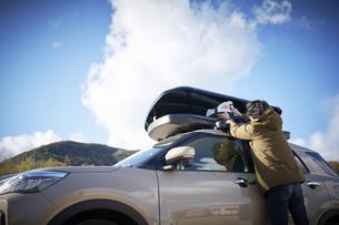 車の上のキャリーボックスに荷物を入れる男性の写真素材 [FYI04782765]