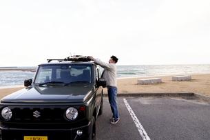車のキャリーにサーフボードをくくりつける男性の写真素材 [FYI04782769]