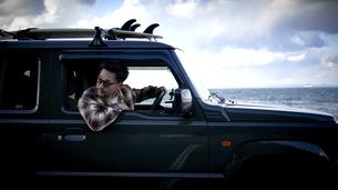 車の窓から体を乗り出して後方を見る男性の写真素材 [FYI04782770]