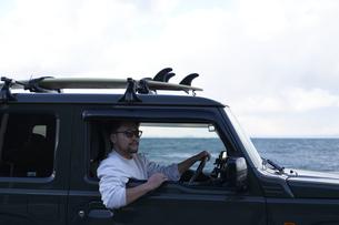 車の窓に肘を置き外を見る男性の写真素材 [FYI04782771]