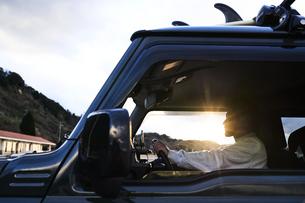 逆光の光を浴びた車を運転する男性の写真素材 [FYI04782772]
