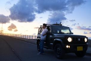 車を停めて夕暮れを眺める男性の写真素材 [FYI04782773]