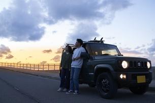 車を停めて夕暮れを眺める男女の写真素材 [FYI04782776]