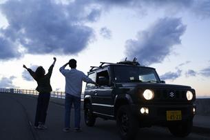 車を停めて夕暮れを眺める男女の写真素材 [FYI04782778]