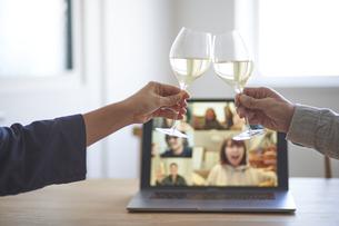 男女が乾杯をする手とリモート飲みをするパソコンの画面の写真素材 [FYI04782796]